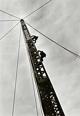workers climb a construction tower