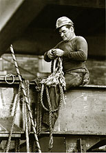 a steel worker sits on a beam
