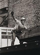 An ironworker signals co-workers